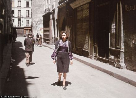 A woman walks a Parisian backstreet, in front of an older gentleman with the Star of David