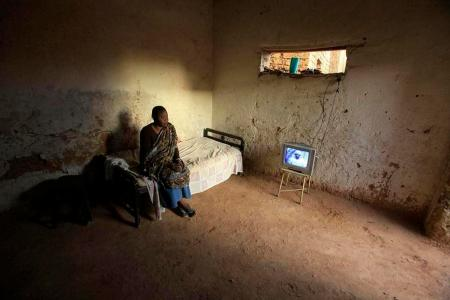 A woman watches television in her house in the outskirts of Sudan's capital, Khartoum April 5, 2010. REUTERS/Zohra Bensemra (SUDAN - Tags: SOCIETY IMAGES OF THE DAY)