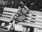 A Jewish woman who is concealing her face sits on a park bench marked Only for Jews, Austria, 1938.