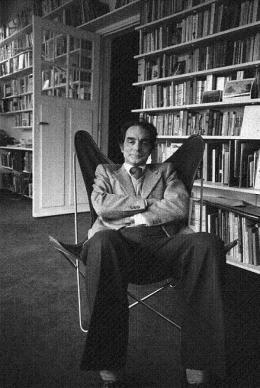 Italo Calvino sentado en una BKF en su biblioteca